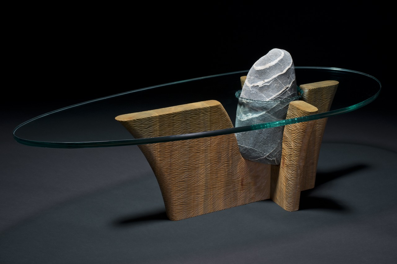 Stone and wood coffee table hand carved with a glass top by Seth Rolland Custom Wood Furniture