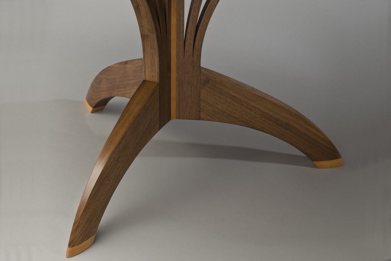 Detail of Arbol cafe table base in carved walnut and cherry by Seth Rolland custom furniture design