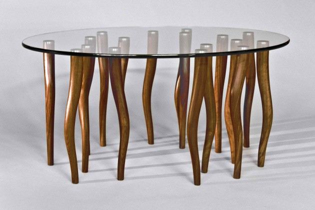Organic, contemporary coffee table made from solid walnut wood and elliptical glass with stainless steel.