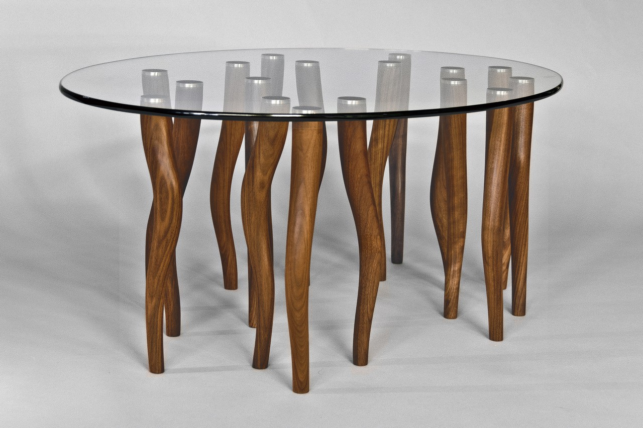Oval glass coffee table with wood and stainless steel legs carved by Seth Rolland custom furniture