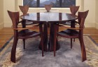 Round walnut dining table with Finback armchairs and expanding table by Seth Rolland custom furniture design