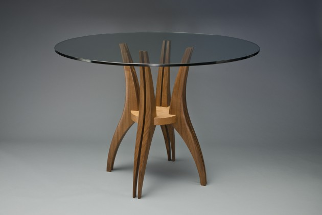 Round cafe table with wood base and glass top hand carved by Seth Rolland custom furniture design