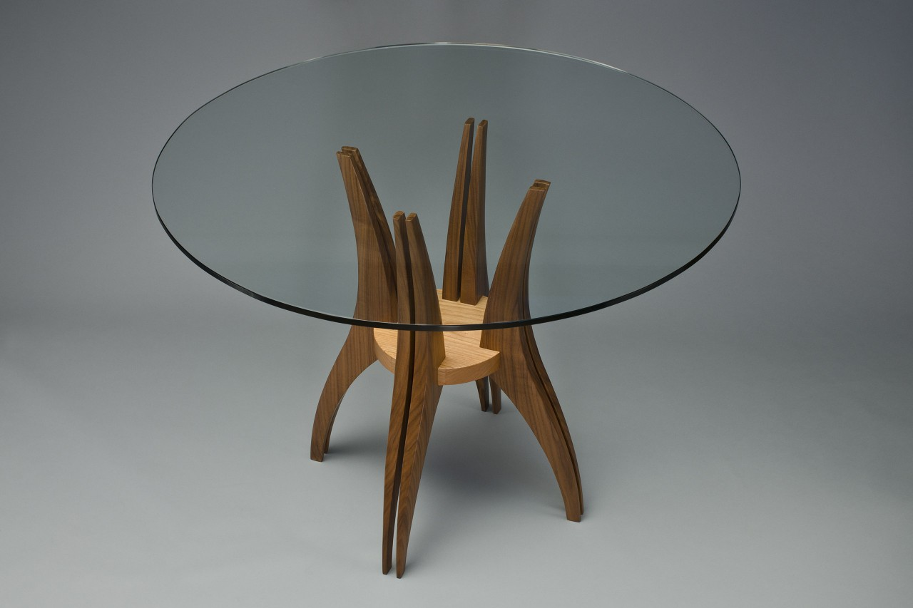 Round glass top wood dining cafe table with curved sculpted legs by Seth Rolland custom furniture design