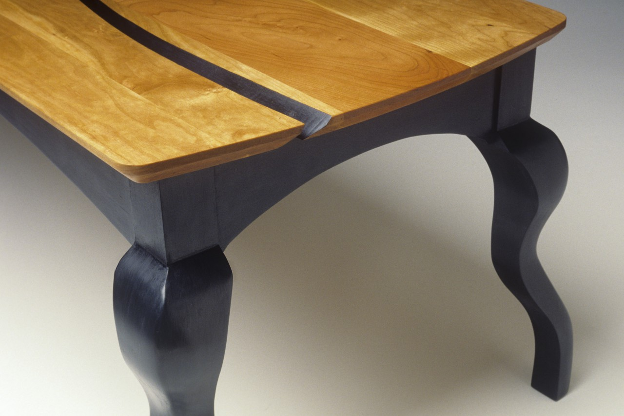 Detail of cherry and milk paint coffee table with carved cabriole legs by Seth Rolland custom furniture design
