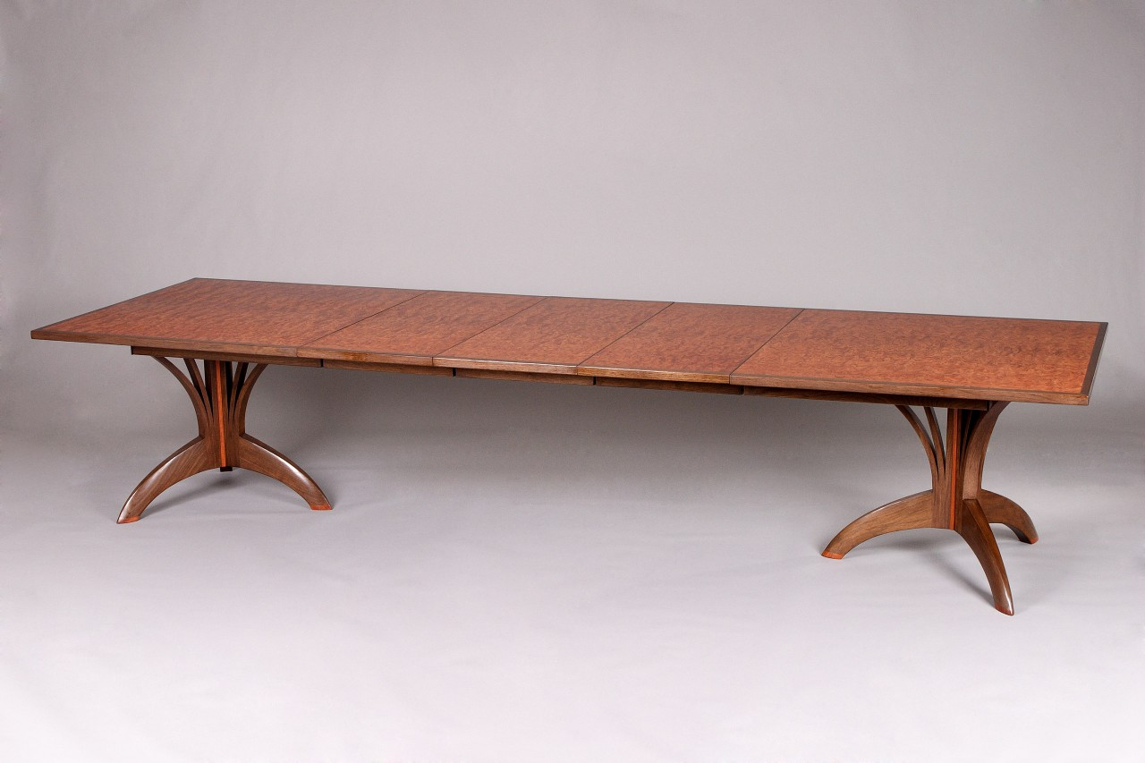 expanding dining table with leaves and custom carved base by Seth Rolland fine furniture design