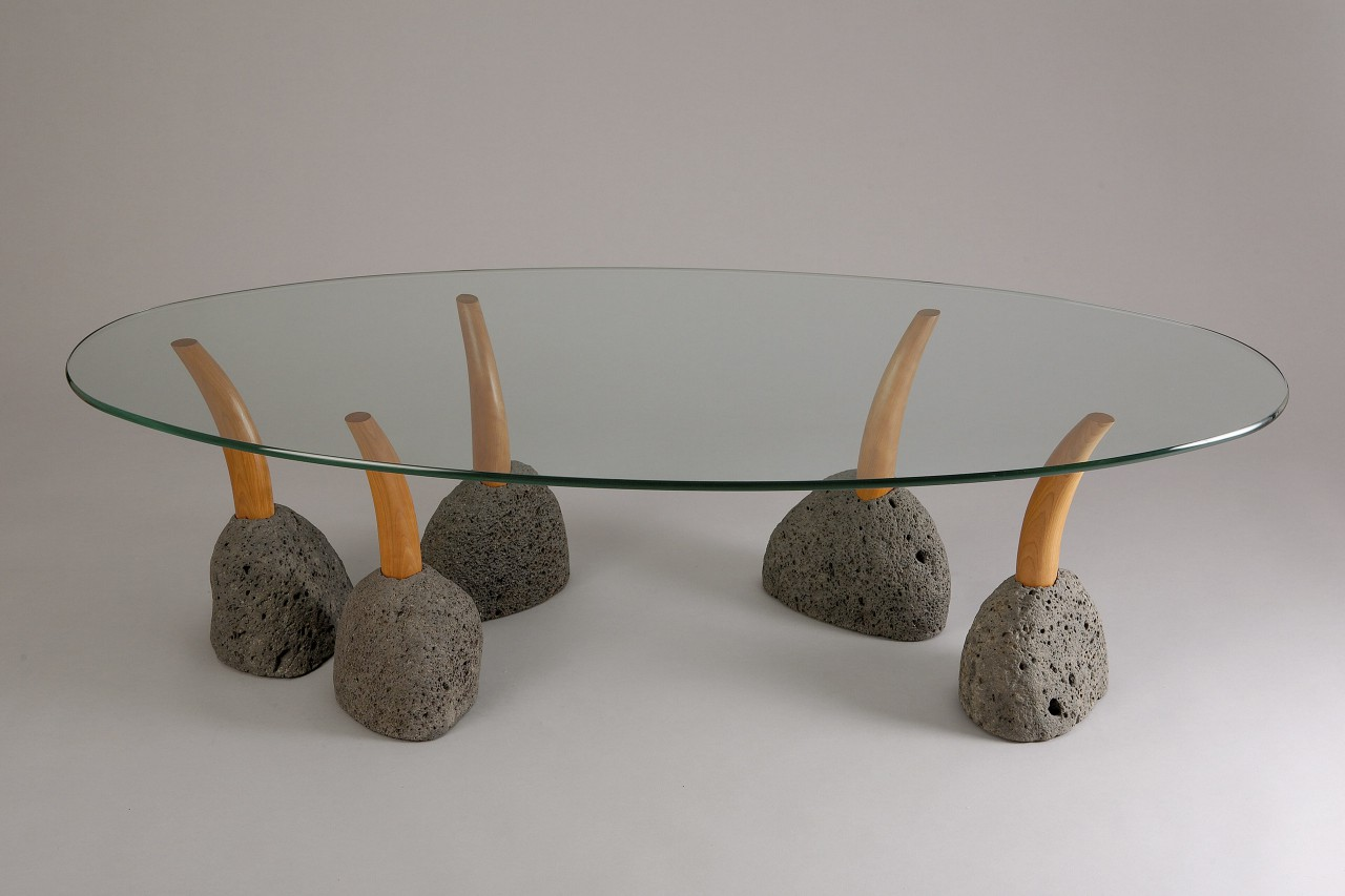 Oval glass top modern coffee table with interactive stone and wood legs by Seth Rolland custom furniture design