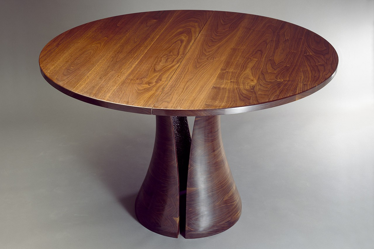 Round walnut dining table with solid carved base expands with leaves by Seth Rolland custom furniture design