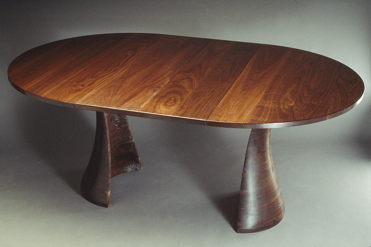 Expanding oval wood dining table in solid walnut by Seth Rolland custom furniture design
